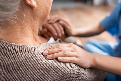 massage therapist hands on shoulder elderly homebound patient